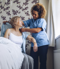 nurse dressing an elderly