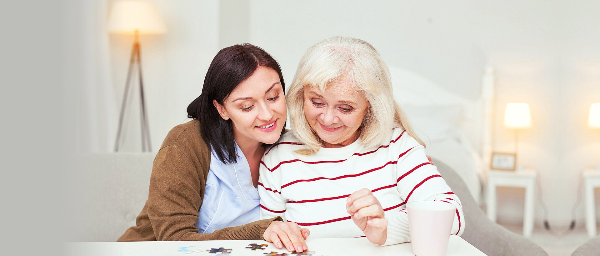 nurse and elderly woman playing jigsaw puzzle