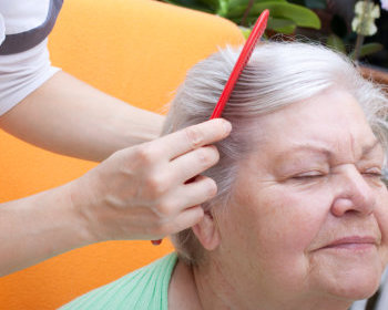 nurse combing an elderly's hair